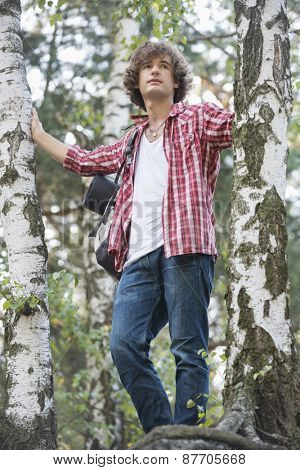 Young male hiker standing in forest
