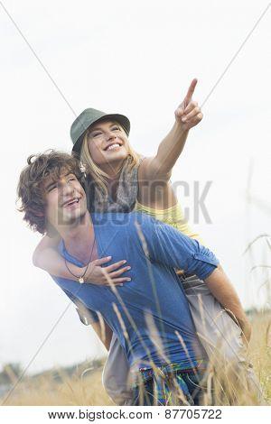 Cheerful woman showing something while enjoying piggyback ride on man in field