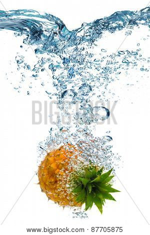 Fresh pineapple dropped into water with splash isolated on white
