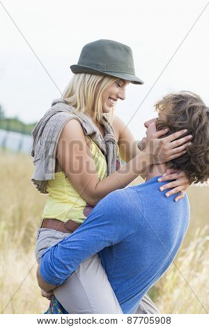 Romantic man carrying woman in field