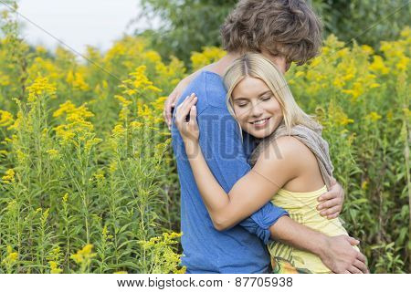 Side view of affectionate couple hugging in field