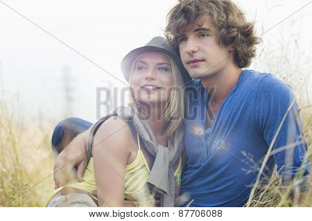 Romantic young couple looking away while sitting in field