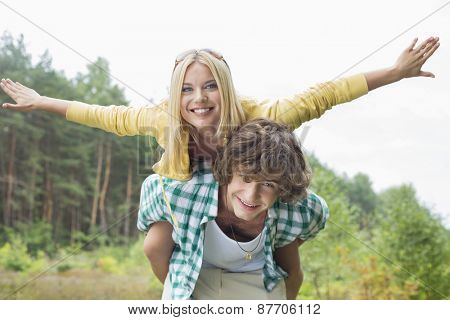 Portrait of happy woman enjoying piggyback ride on man in forest
