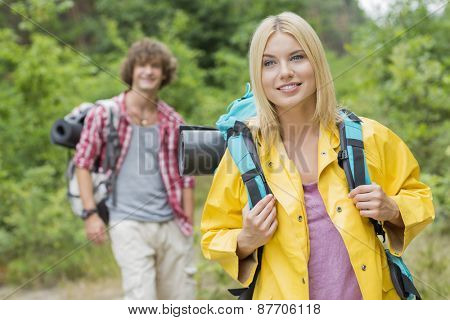 Smiling female backpacker looking away with man standing in background at forest