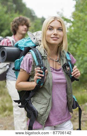 Beautiful female backpacker looking away with man standing in background at forest