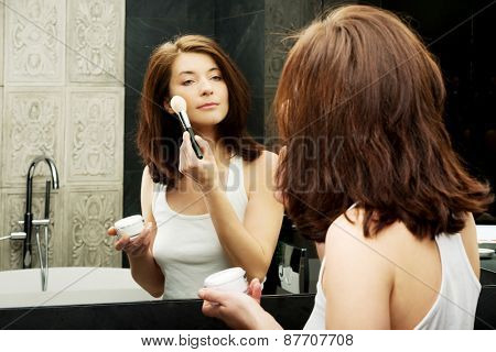 Beautiful woman doing make up in bathroom.