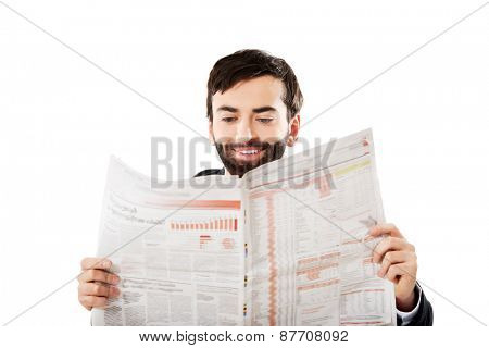 Young businessman reading newspaper in the office.