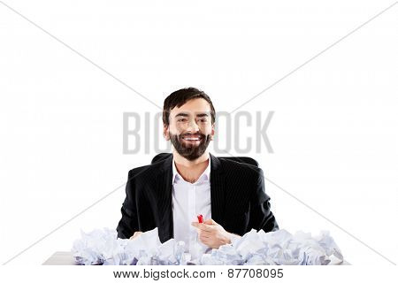 Young successful businessman sitting with crushed sheets.