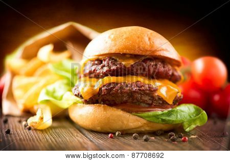 Hamburger with fries on wooden table. Cheeseburger on fresh buns with succulent beef patties and fresh salad ingredients served with French Fries in crumpled brown paper on a wooden table