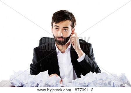 Young thoughtful businessman sitting with crushed sheets.