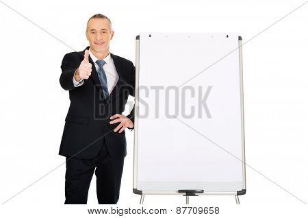 Mature businessman with ok sign near flip chart