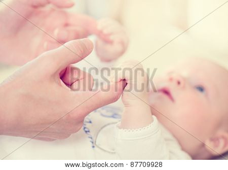 Parent holding newborns hand. Hand in hand. Mother and her Newborn Baby. Happy Mother and Baby together. Maternity concept. Parenthood. Motherhood