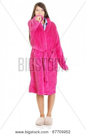 Beautiful woman wearing pink bathrobe pointing on you.