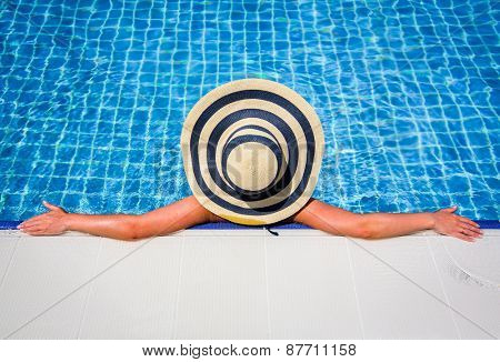 Woman in straw hat relaxing swimming pool. Bottom composition perfect copy space for your text ads.