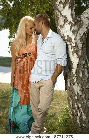 Young casual caucasian man embracing attractive blonde female outdoor. Leaning against tree, hands in pocket.