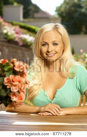 Portrait of attractive young blonde busty caucasian woman sitting at table, outdoors in a summer garden with flowers. Smiling.