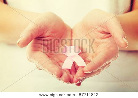 Womans hands holding pink breast cancer awareness ribbon