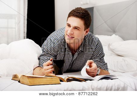 Handsome happy man with a book in his bed.