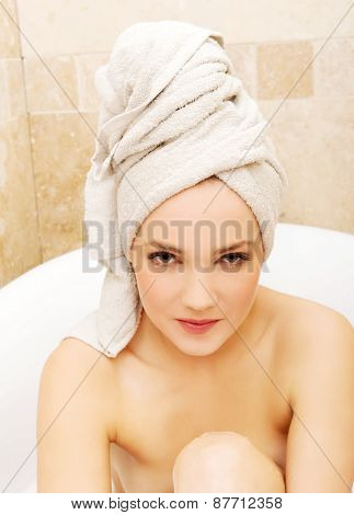 Young spa woman sitting in bathtub.
