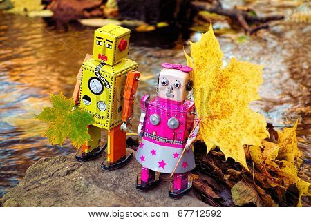 Robots collecting autumn leaves by the river