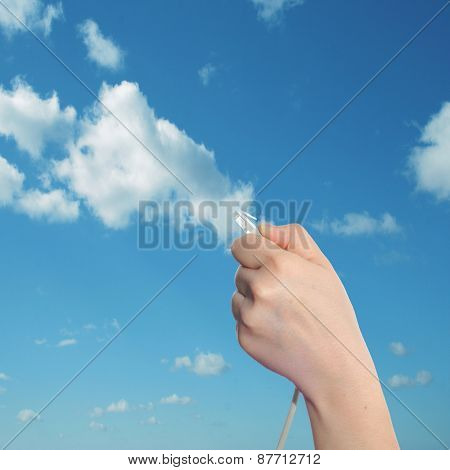 Conceptual human or man hand holding a internet or data cable in clouds over the blue sky background