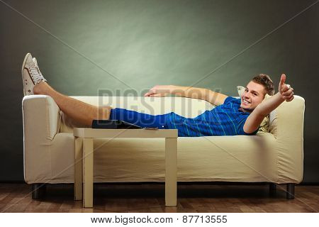 Young Man Relaxing On Couch Making Thumb Up