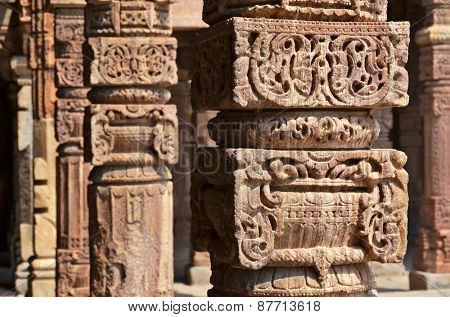 Columns with stone carving in courtyard of Quwwat-Ul-Islam mosque, Qutab Minar complex, Delhi, India