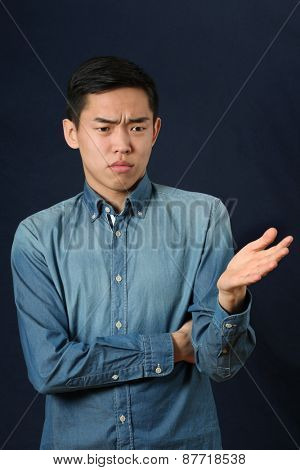 Displeased young Asian man gesturing with one hand