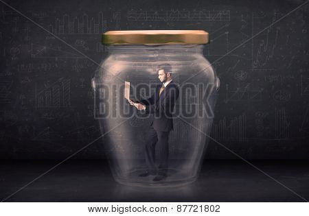 Business man closed into a glass jar concept on background