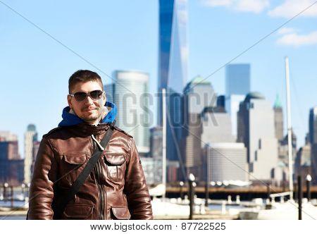 Man in New York City with Manhattan skyline at background