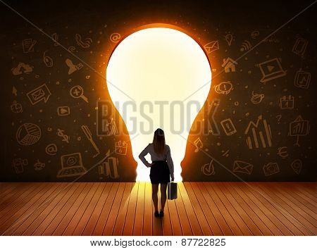 Business woman looking at bright light bulb in the wall concept