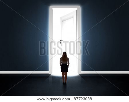 Business woman looking at big bright opened door concept