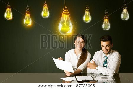 Business couple sitting at the black table with idea bulbs on the background