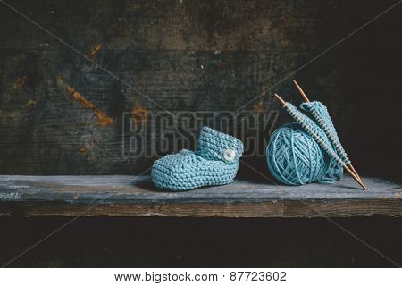 Knitting baby shoes with blue yarn