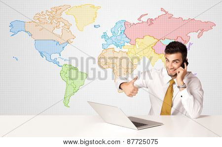Businessman sitting at white table with colorful world map background