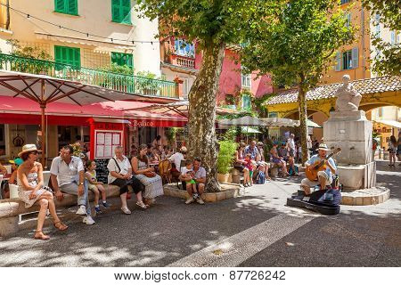 MENTON, FRANCE - AUGUST 15, 2014: People listening to street musician in old town of Menton - popular resort on French Riviera, famous for gardens and Lemon Festival taking place every February.