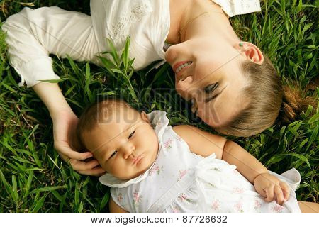 Mother With Caressing Baby Daughter Laying On Grass