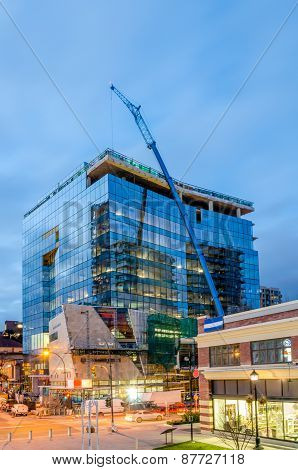 High-rise glass building under construction. The site with crane against evening sky.