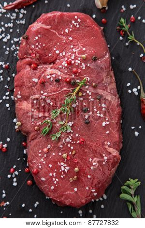 Raw beef rump steak on black table, close-up