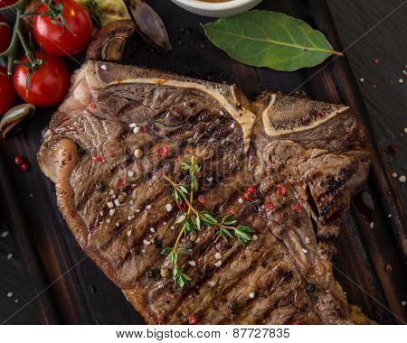 Beef t-bone steak on black stone table, close-up.