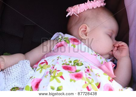 Peaceful Baby In Dress And Hat Lying In Black Baby Stroller And Sleeps