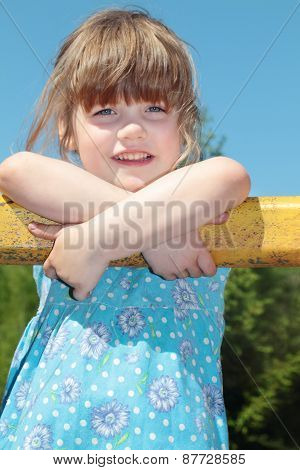 Beautiful Cute Little Girl In Blue Dress Rests Hands On Yellow Tube