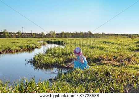 Beautiful Cute Little Girl In Blue Dress Sitting By Creek With Stick In Hand