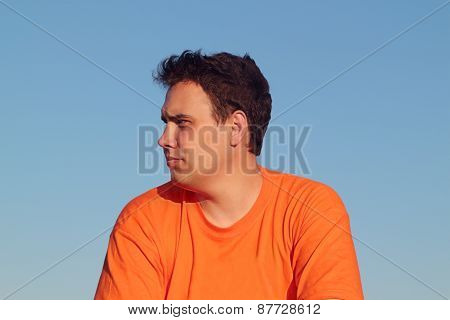 Handsome Young Man In Orange Shirt Thoughtfully Looking Away On Summer Day