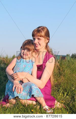 Smiling Mom With Her Daughter Sitting On Grass In Summer Sunny Day
