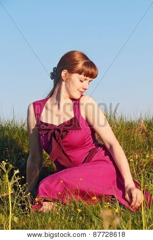 Beautiful Girl In Pink Dress Sitting On Grass In Sunny Summer Day