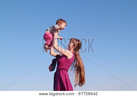 Beautiful Smiling Young Woman In Pink Dress Holding Her Son On Sky Background