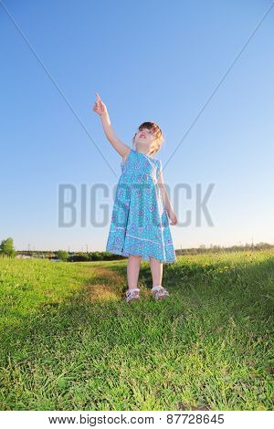 Little Cute Girl In Blue Dress Standing On Grass And Shows Up