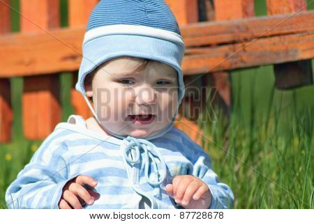 Close-up Of Cute Little Boy In Blue Striped Suit And Hat Sitting Next To Fence