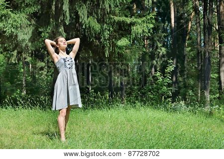 Beautiful Girl In Dress Corrects Hair Standing On Grass On Sunny Summer Day